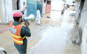 RAWALPINDI: August 27 - A rescue worker making announcement through megaphone to warn residents of the flooded area following monsoon rain and  overflowed Nullah Lai passing through the area triggered floods and forcing people to move along with their belongings to safer places in the outskirts of the city. APP photo by Abid Zia