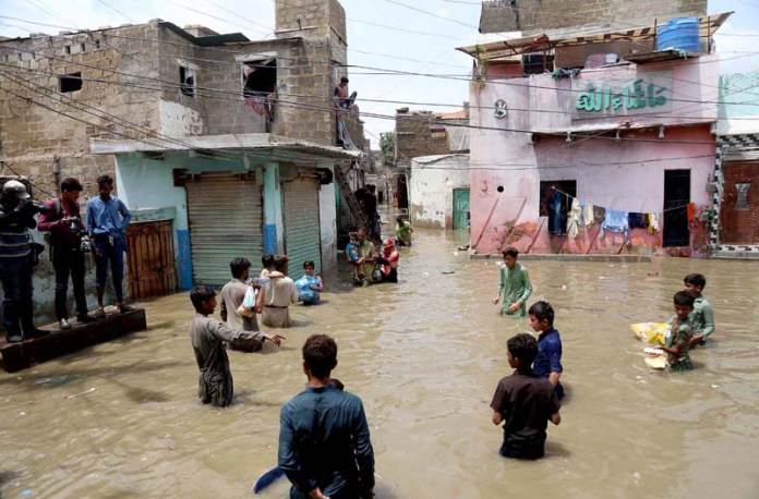 KARACHI: August 22 - Families moving to safer place a Ayub Goth Surjani town has submerged in rain water after heavily downpour in the city. APP photo by M Saeed Qureshi