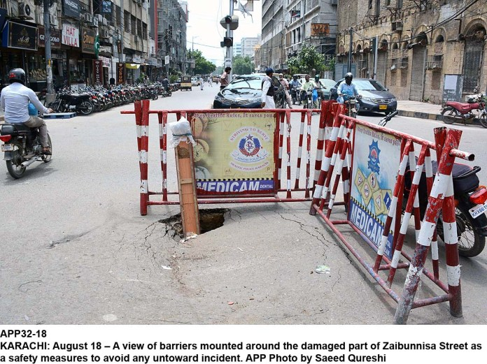 KARACHI: August 18 – A view of barriers mounted around the damaged part of Zaibunnisa Street as a safety measures to avoid any untoward incident. APP Photo by Saeed Qureshi