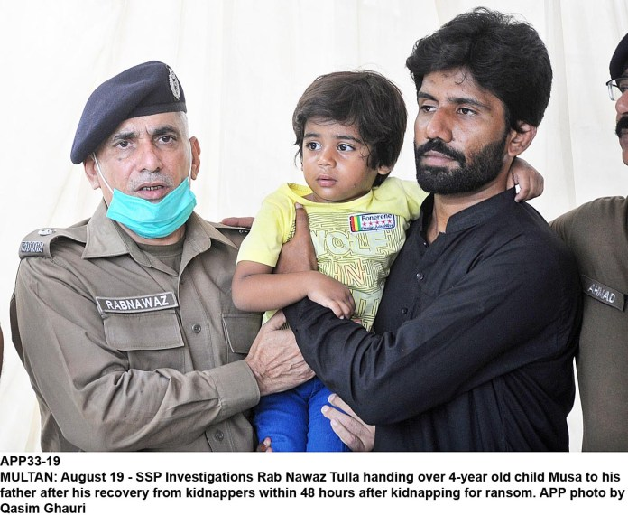 MULTAN: August 19 - SSP Investigations Rab Nawaz Tulla handing over 4-year old child Musa to his father after his recovery from kidnappers within 48 hours after kidnapping for ransom. APP photo by Qasim Ghauri