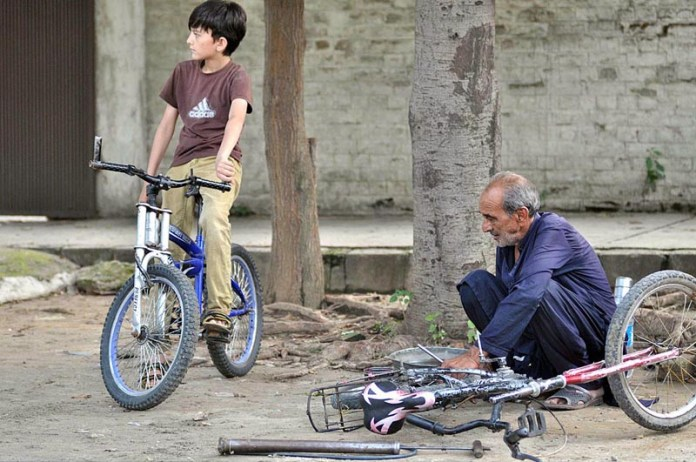 ISLAMABAD: August 20 – An old man busy in repairing bicycles at his roadside setup in G6 area. APP photo by Irshad Sheikh