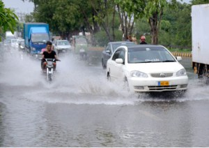 LAHORE: August 27 - Motorcyclist passing through rain water accumulated on the road during rain in provincial capital. APP Photo by Ashraf Ch