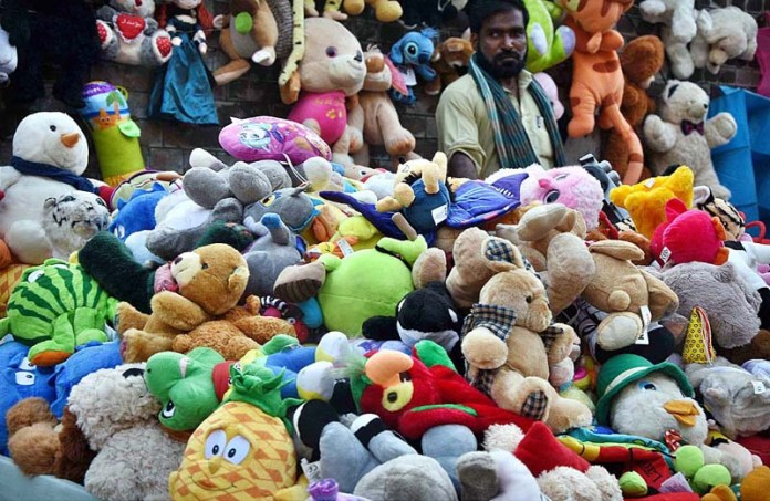 LAHORE: August 25 - A vendor waiting for customers to sell second hand toys at his roadside setup in Provincial Capital. APP Photo by Mustafa Lashari