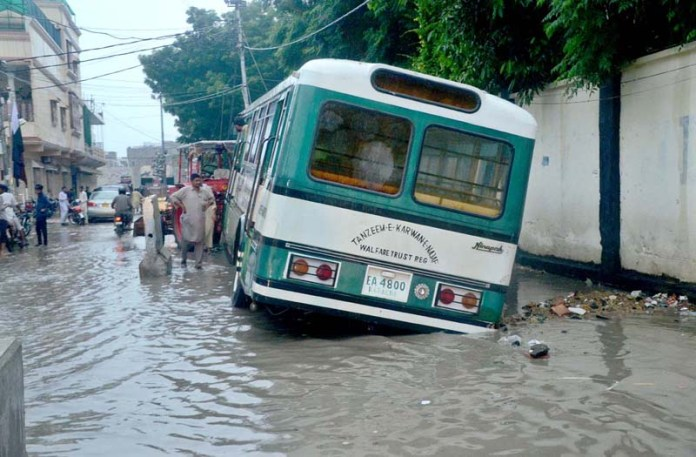 KARACHI: August 21 - A passenger bus stranded in flooded water accumulated on the road during heavy rain in provincial capital City. APP photo by Syed Abbas Mehdi