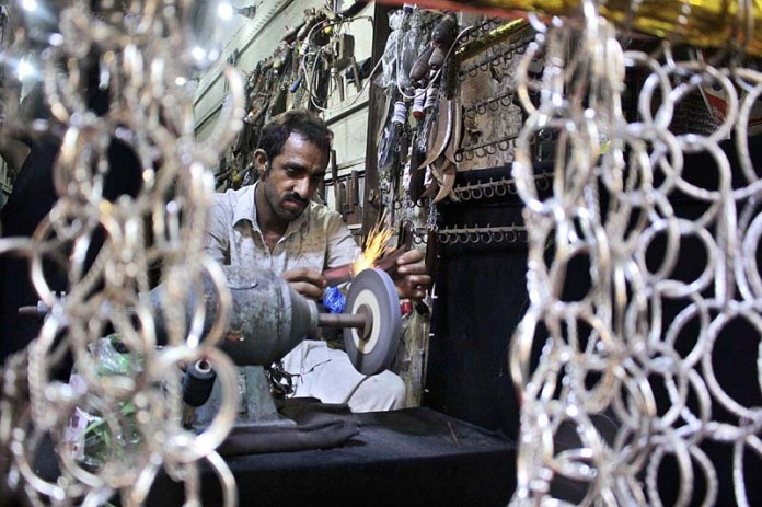 LAHORE: August 26 - A blacksmith sharpening knives to be used by mourners oozing themselves during procession of Muharram. APP photo by Rana Imran
