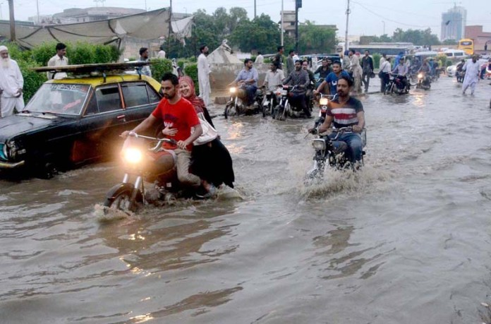 KARACHI: August 21 - Motorcyclists passing through flooded water accumulated on the Shahrah-e-Pakistan road during heavy rain in the provincial capital. APP photo by Syed Abbas Mehdi