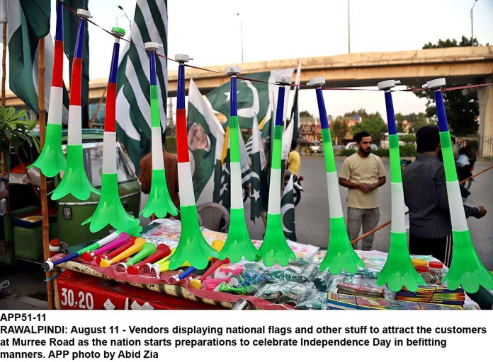 RAWALPINDI: August 11 - Vendors displaying national flags and other stuff to attract the customers at Murree Road as the nation starts preparations to celebrate Independence Day in befitting manners. APP photo by Abid Zia