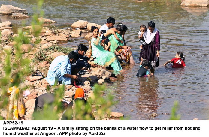 ISLAMABAD: August 19 – A family sitting on the banks of a water flow to get relief from hot and humid weather at Angoori. APP photo by Abid Zia