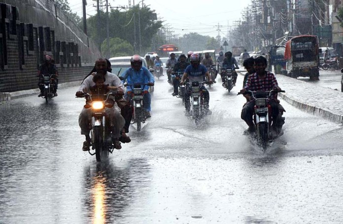 LAHORE: August 26 – Motorcyclist passing through rain water accumulated on the road during rain in Provincial Capital. APP Photo by Ashraf Ch