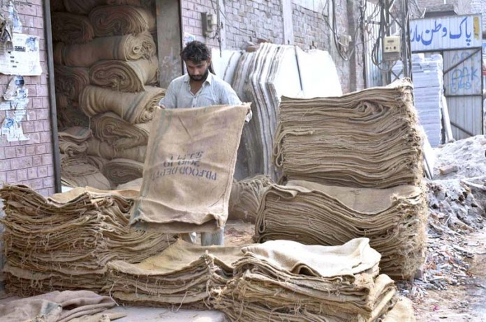 FAISALABAD: September 19 - A laborer is grading jute bags before the sale in the market. APP photo by Muhammad Waseem