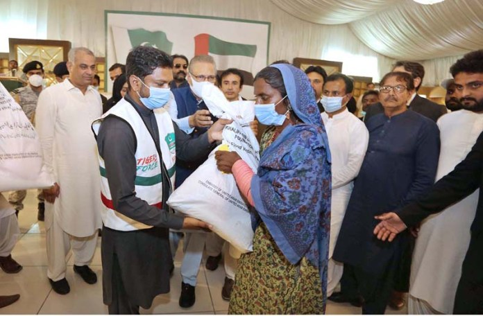 MIRPUUKHAS: September 12 – President Dr. Arif Alvi along with Governor Sindh Imran Ismail distributes Rashan to affected people donated by Sheikh Khalifa Bin Zayed Al Nahiyan Foundation during his visit to flood affected areas. APP photo by Akram Ali