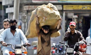 RAWALPINDI: September 14 - A gypsy person on the way carrying a sack filled with recycling items at Iqbal Road. APP photo by Abid Zia