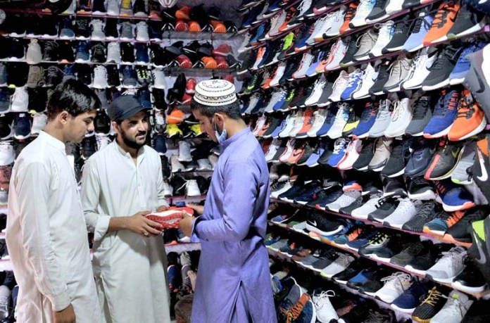 ISLAMABAD: September 27 – People purchasing shoes from a vendor at Sunday Bazar Peshawar Morr. APP photo by Saeed-ul-Mulk