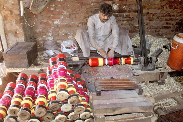 MULTAN: September 13 – Worker busy in coloring on the part of traditional bed (charpai) at his workplace. APP photo by Tanveer Bukhari