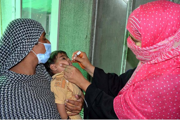FAISALABAD: September 22 - A health worker administering polio drops to a child at Mian Muhammad Trust Hospital during 5-day anti-polio drive in the city. APP photo by Tasawar Abbas