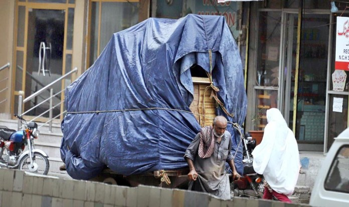 RAWALPINDI: September 03 - An elderly labourer on the way pulling hand cart loaded with luggage to be delivered at shops at Committee Chowk. APP photo by Abid Zia