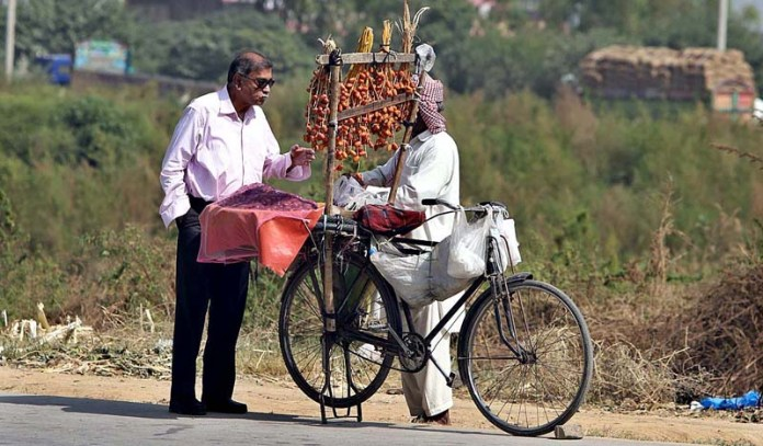 RAWALPINDI: September 29 - A customer purchasing fresh dates displayed by a street vendor displaying on his bicycle at Dhoke Hassu. APP photo by Abid Zia