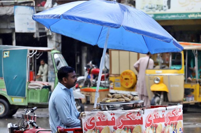 RAWALPINDI: September 03 - A vendor under the cover of umbrella displaying sweet potatoes to attract customers at Iqbal Road. APP photo by Abid Zia