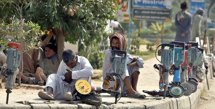 RAWALPINDI: September 29 - Labourers along with their tools sitting at a roadside waiting for daily job at Peshawar Road. APP photo by Abid Zia