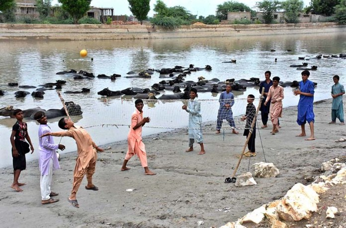LARKANA: September 01 – Youngsters playing volleyball at Rice Canal. APP photo by Nadeem Akhtar