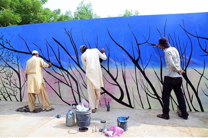 HYDERABAD: September 16 – Painters painting on the wall at Hilltop Road to add beautification in the Cantonment area. APP photo by Farhan Khan