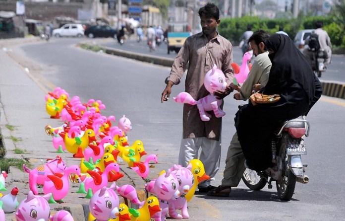 MULTAN: September 11 - A vendor displaying and selling plastic toys to attract the customer near Eidgah Chowk. APP photo by Qasim Ghauri