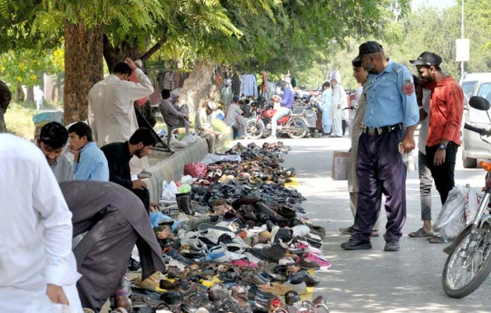 ISLAMABAD: September 19 - People busy in selecting second hand shoes from vendor's roadside setup near at Abpara Market. APP photo by Saeed-ul-Mulk