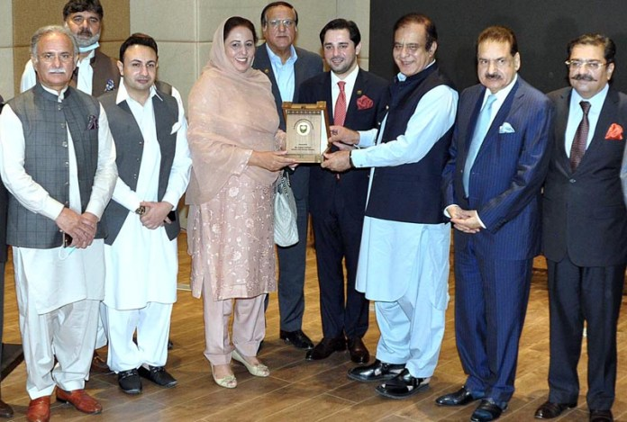 ISLAMABAD: September 16 - Federal Minister for Information and Broadcasting Senator Shibli Faraz giving a shield to MNA Ms. Sajida Zulfiqar during the inaugural ceremony of Auditorium Export Display Centre at EDC Building. APP Photo by Irshad Sheikh