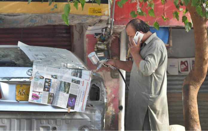 ISLAMABAD: September 29 - A painter painting a vehicle at his workplace at G-7 market. APP photo by Irshad Sheikh