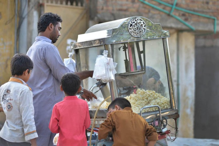 ISLAMABAD: September 30 – A street vendor roasting corns to attract the customers. APP photo by Irshad Sheikh