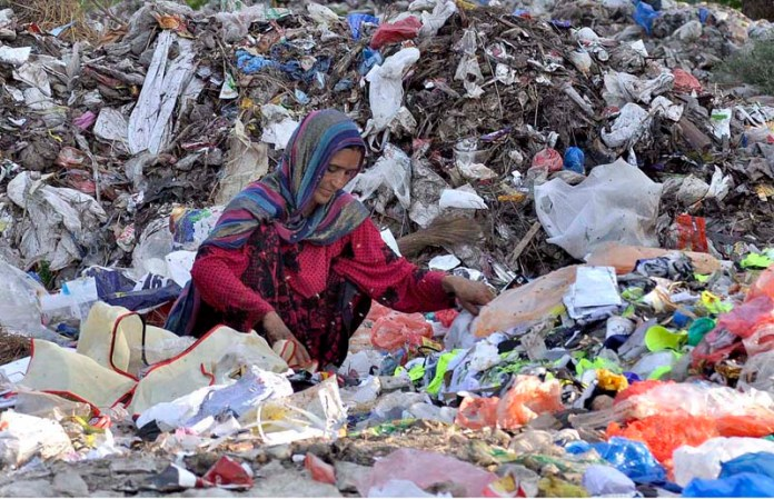 ISLAMABAD: September 19 – A gypsy female searching valuables from heap of garbage. APP photo by Saleem Rana