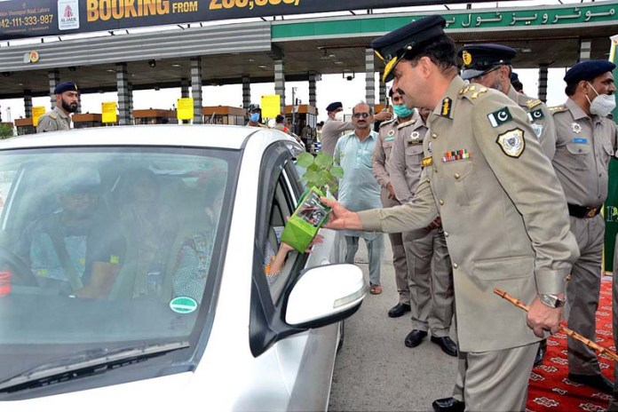 LAHORE: September 01 - DIG Motorway Police Mehboob Aslam Lilla distributing plant among the people during Prime Minister Clean and Green Pakistan Campaign. APP Photo by Ashraf Ch