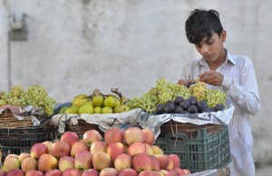 ISLAMABAD: September 21 – A youngster displays fruits to attract the customers at his roadside setup at Aabpara market. APP photo by Irshad Sheikh