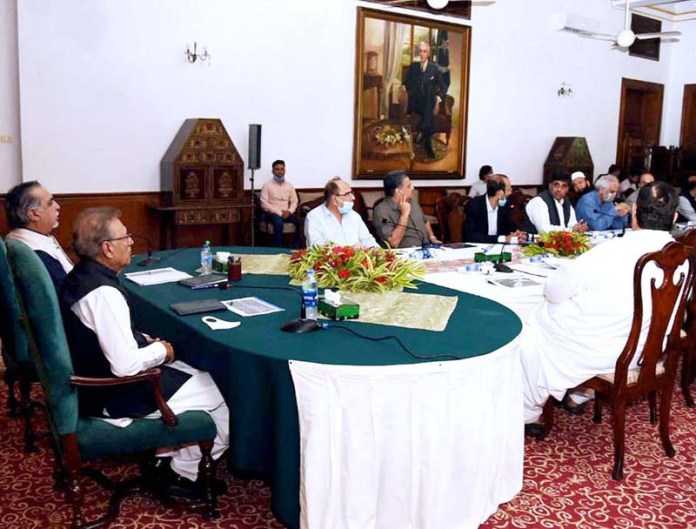 KARACHI: September 13 – President Dr. Arif Alvi chairing a meeting of business community at Governor House. Governor Sindh Imran Ismail is also present. APP