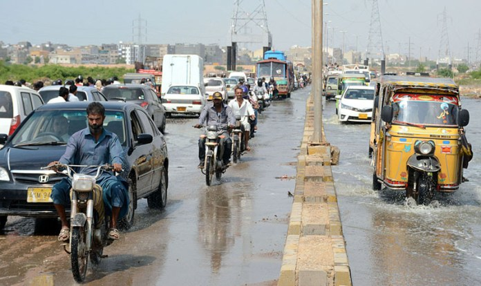 KARACHI: September 16 – A view of traffic on the way from flooded road at Korangi due to overflow of Malir River. APP Photo by Saeed Qureshi