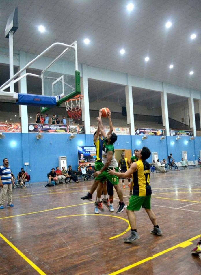 SARGODHA: September 27 - A view of Basket Ball match playing between International 11 and Youth 11 during Deputy Commissioner Floodlight Basket Ball Tournament organized by Sports Department at Sports Gymnasium. APP photo by Hassan Mahmood