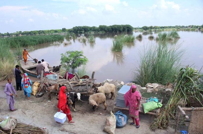 MULTAN: September 03 - Flood affected families unloading their household items from boat. APP photo by Tanveer Bukhari