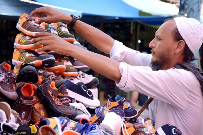KARACHI: September 17 - A vendor displaying and arranging footwear to attract customers at Bohri Bazaar. APP Photo by Saeed Qureshi