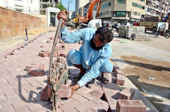 KARACHI: September 08 – A labourer cutting the bricks for the construction of footpath during the maintenance work in the city. APP Photo by Saeed Qureshi