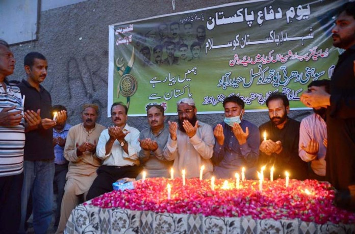 HYDERABAD: September 05 – Members of Sohni Dharti Youth Council offering dua after lights-up the candles to pay tributes to the martyrs of Pak Army in connection with Defence & Martyrs Day of Pakistan outside Press Club. APP photo by Farhan Khan