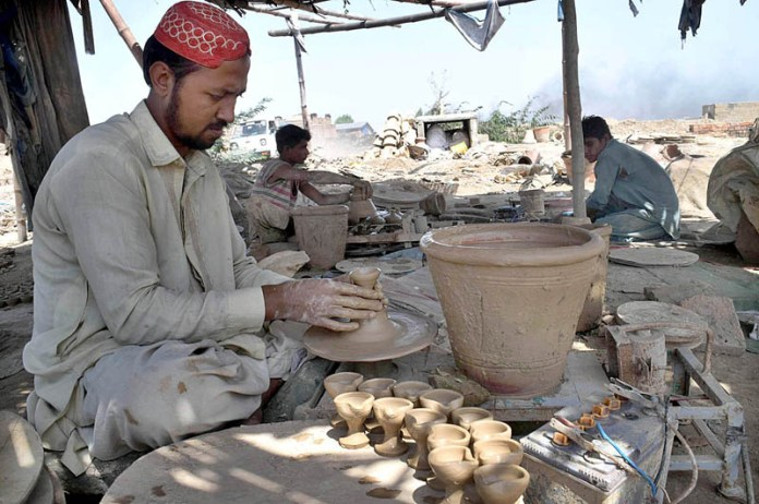 KARACHI: September 29 – Labourers preparing clay-made pots in a traditional way at his workplace. APP Photo by Abbas Mehdi