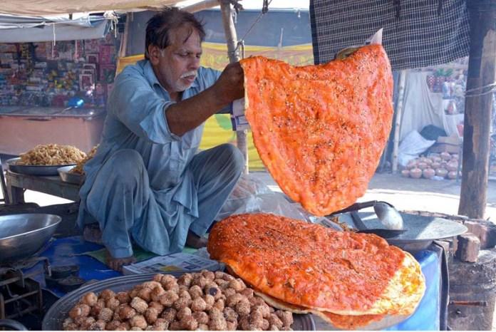 FAISALABAD: September 18 - A vendor preparing and displaying katlamas to attract the customers on his roadside setup. APP photo by Tasawar Abbas