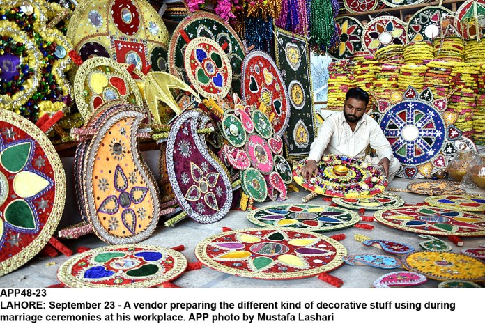 LAHORE: September 23 - A vendor preparing the different kind of decorative stuff using during marriage ceremonies at his workplace. APP photo by Mustafa Lashari