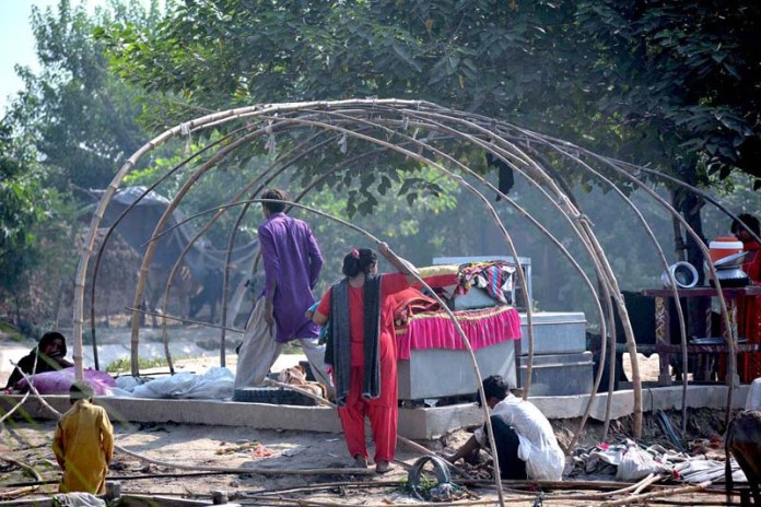 FAISALABAD: September 18 - A gypsy family preparing their makeshift hut. APP photo by Tasawar Abbas