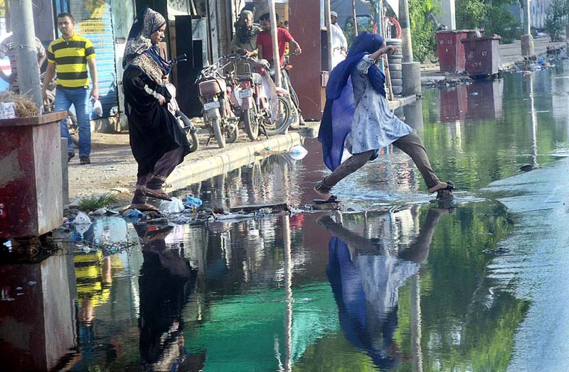 KARACHI: September 09 - Women crossing stagnant sewerage water accumulated at Jahangir Road due to choked drainage system after heavy rain in city and needs the attention of concerned authorities. APP Photo by Abbas Mehdi