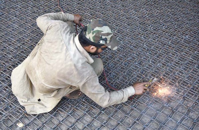 LAHORE: September 07 - Worker busy in welding the iron grill at their workplace in Provincial Capital. APP Photo by Mustafa Lashari