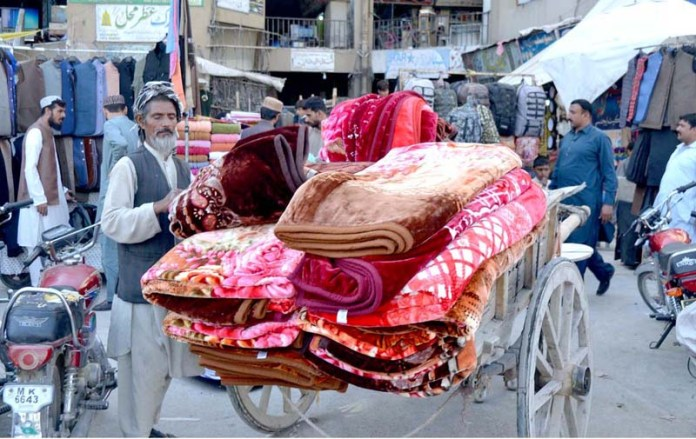 QUETTA: September 10 – A labourer loading blankets to supply to shopkeepers at Meezan Chowk. APP photo by Mohsin Naseer