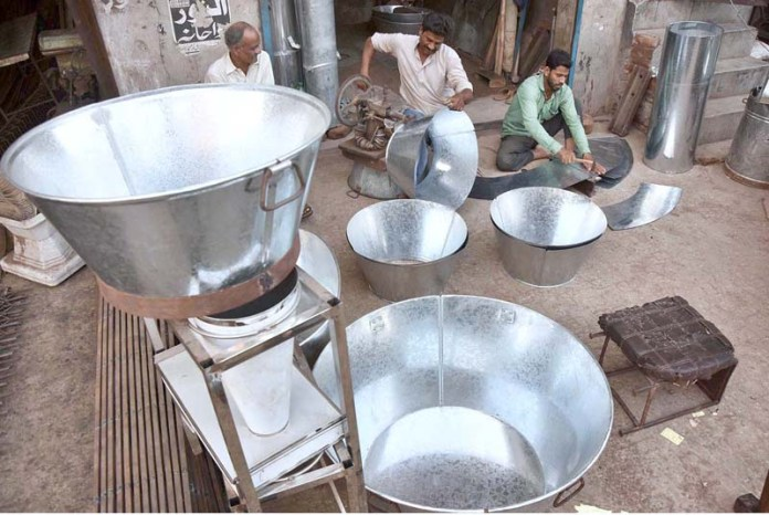LAHORE: September 07 - Workers busy in preparing the stainless steel tub at their workplace in Provincial Capital. APP Photo by Mustafa Lashari