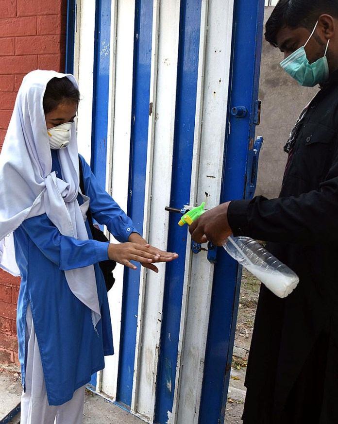 LAHORE: September 15 - A staffer sanitizing the hands of students at the entrance as a large number of the students resumed their academic activities after reopening of higher education institutions in the country joined their educational institutions on Tuesday after around six-month long closure due to the corona virus pandemic. APP photo by Mustafa Lashari