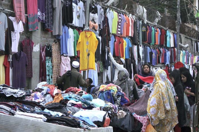 LAHORE: September 10 - Ladies selecting and purchasing old clothes from a roadside shop near Meo Hospital. APP photo by Rana Imran